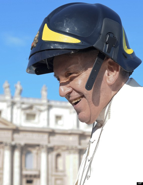 In this picture provided Wednesday, Oct. 16, 2013, by the Vatican newspaper L'Osservatore Romano, Pope Francis wears a firefighter's helmet he was given as he arrived for his weekly general audience at the Vatican. (AP Photo/L'Osservatore Romano, ho)