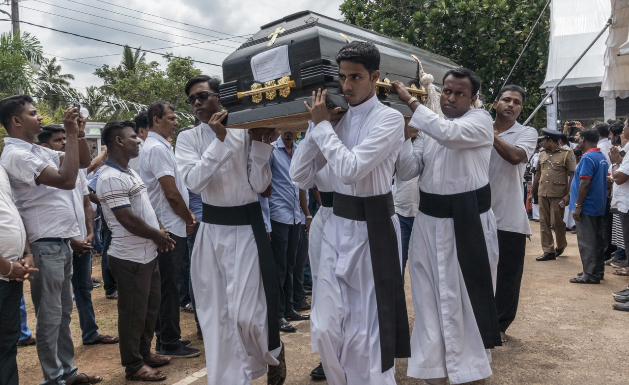 Men carrying a casket to the grave